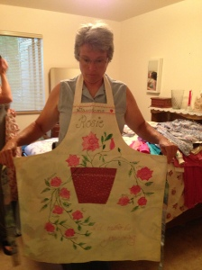 girl wearing apron with applique of flower pot with rose plant and the name Rosie